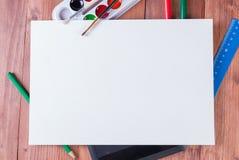 Le comprimé, les peintures, les crayons et les marqueurs sous une feuille de livre blanc avec l'espace de copie Photo libre de droits