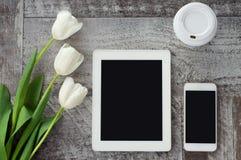 Le comprimé, le téléphone, le café et les fleurs blancs sont sur la table Travail ? la maison ind?pendant photos stock