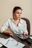 Le comptable de jeune femme considère sur la calculatrice Photographie stock libre de droits