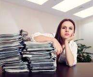 Le comptable féminin étreint de grandes piles de documents Photographie stock