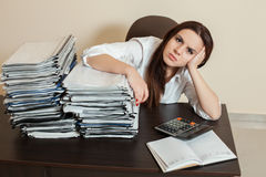 Le comptable féminin étreint de grandes piles de documents Photo stock