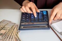 Le comptable féminin considère des dollars sur une calculatrice dans le workp Photographie stock