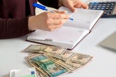 Le comptable féminin remplit rapports d'argent liquide dans le lieu de travail Photo stock
