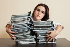 Le comptable fatigué étreint de grandes piles de documents Image libre de droits