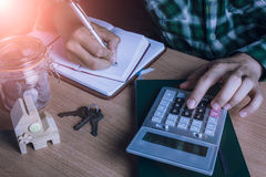 Le comptable ou le banquier asiatique d'homme calculent les finances/épargne argent ou économie pour la maison de loyer Image libre de droits