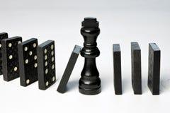 Le concept abstrait d'affaires avec la pièce d'échecs de roi et le domino rapièce tombé Photographie stock