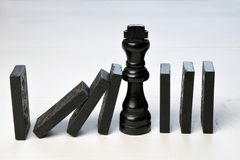 Le concept abstrait d'affaires avec la pièce d'échecs de roi et le domino rapièce tombé Photo stock