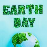 Le concept créatif avec le jour de terre de lettrage d'ensemble en pousses fraîches vertes d'herbe et la partie de la planète mod Image stock
