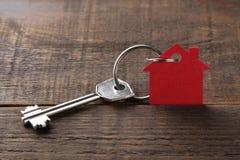 Le concept d'acheter une maison Clés avec la maison de keychain sur un fond en bois brun avec l'espace pour l'inscription photo stock