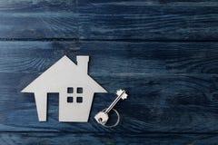Le concept d'acheter une maison Clés décoratives de hutte et de maison sur un fond en bois bleu avec un endroit pour une inscript photos stock