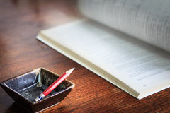 Le concept d'affaires des places met en forme de tasse le crayon et un livre sur le backg en bois Image libre de droits