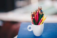 Le concept d'art a coloré des crayons dans un verre sur le livre photo stock
