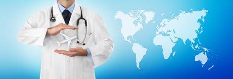 Le concept d'assurance-maladie de voyage, les mains du docteur protègent un avion sur le fond bleu avec la carte, calibre de bann image libre de droits