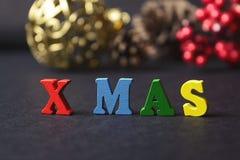 Le concept d'une nouvelle année, Noël Le mot des lettres multicolores sur le fond en bois de Noël avec des cadeaux, cônes de pin, Photo stock