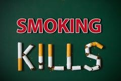 le concept de cigarettes de sang a isolé des mises à mort fumant le blanc Photo stock