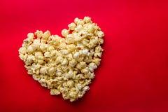 Le concept de cinéma du maïs éclaté a arrangé dans une forme de coeur sur le backg rouge Photos stock