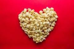 Le concept de cinéma du maïs éclaté a arrangé dans une forme de coeur sur le backg rouge Photo libre de droits
