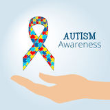 Le concept de conscience d'autisme avec la main tenant le ruban du puzzle rapièce Photos libres de droits