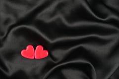 Le concept de deux coeurs d'amants se trouvant sur le satin noir Photographie stock libre de droits