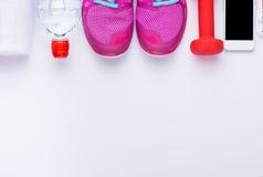 Le concept de forme physique avec le téléphone portable avec la serviette et la femme folâtrent des chaussures au-dessus du fond  Photo libre de droits