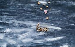 Le concept de jour du ` s de Valentine, les coeurs en bois et le mot aiment sur un fond en bois bleu, la lumière naturelle, l'esp images libres de droits