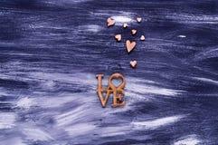 Le concept de jour du ` s de Valentine, les coeurs en bois et le mot aiment sur un fond en bois bleu, la lumière naturelle, l'esp Photographie stock