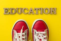 Le concept de l'éducation Exprimez les espadrilles des enfants rouges d'éducation avec le fond jaune Photo libre de droits