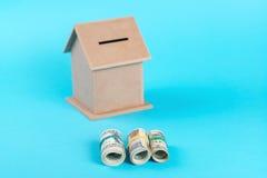 Le concept de l'épargne financière pour acheter une maison Tirelire, dollars en petits pains, d'isolement sur le fond bleu Photographie stock