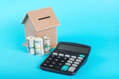 Le concept de l'épargne financière pour acheter une maison Tirelire, dollars et calculatrice sur le fond bleu Images libres de droits