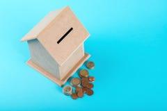 Le concept de l'épargne financière pour acheter une maison Tirelire et pièces de monnaie d'isolement sur le fond bleu Photos stock