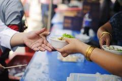 Le concept de l'alimentation : Les mains des pauvres re?oivent la nourriture des mains de l'humanitaire : Aide pour alimenter les photo libre de droits