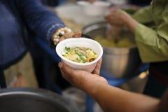 Le concept de l'alimentation : Les mains des pauvres re?oivent la nourriture des mains de l'humanitaire : Aide pour alimenter les image libre de droits