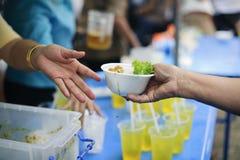 Le concept de l'alimentation : Les mains des pauvres re?oivent la nourriture des mains de l'humanitaire : Aide pour alimenter les photos libres de droits