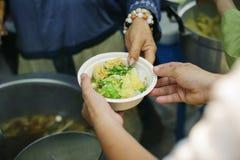 Le concept de l'alimentation : Les mains des pauvres re?oivent la nourriture des mains de l'humanitaire : Aide pour alimenter les photographie stock