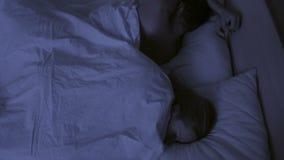 Le concept de l'insomnie, les lancers de couples dans le sien dorment, une vue supérieure banque de vidéos