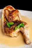 Le concept de la cuisine géorgienne À moitié un poulet cuit au four en sauce à ail avec la croûte croustillante d'un plat blanc,  photo stock