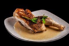 Le concept de la cuisine géorgienne À moitié un poulet cuit au four en sauce à ail avec la croûte croustillante d'un plat blanc,  photos stock