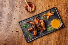 Le concept de la cuisine indienne Ailes et jambes de poulet cuites au four en sauce à moutarde de miel plats de portion dans le r photos libres de droits