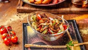 Le concept de la cuisine indienne Salade chaude avec du boeuf et poulet, paprika et sauce en bon état à miel Plats de portion dan images stock