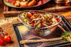 Le concept de la cuisine indienne Salade chaude avec du boeuf et poulet, paprika et sauce en bon état à miel Plats de portion dan image libre de droits