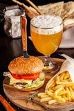 Le concept de la cuisine italienne Hamburger italien avec des pommes frites sur un panneau en bois et un verre de bière blonde av photo stock