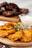 Le concept de la cuisine ukrainienne Draniki des pommes de terre et des potirons, avec les fleurs comestibles Photo libre de droits