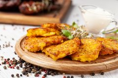 Le concept de la cuisine ukrainienne Draniki des pommes de terre et des potirons, avec les fleurs comestibles Photos libres de droits