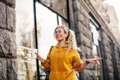 Le concept de la mode de rue jeunes jeans de port élégants de boyfrend d'étudiante, sweetshot jaune lumineux d'espadrilles blanch Photos stock