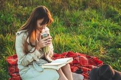 Le concept de la récréation extérieure de mode de vie en automne La fille avec le chapeau a lu des livres sur le plaid avec une t photographie stock