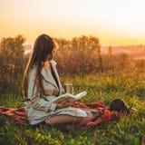Le concept de la récréation extérieure de mode de vie en automne La fille avec le chapeau a lu des livres sur le plaid avec une t images libres de droits