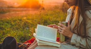 Le concept de la récréation extérieure de mode de vie en automne La fille avec le chapeau a lu des livres sur le plaid avec une t photos stock