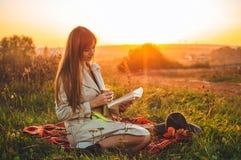 Le concept de la récréation extérieure de mode de vie en automne La fille avec le chapeau a lu des livres sur le plaid avec une t photos libres de droits