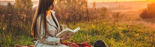 Le concept de la récréation extérieure de mode de vie en automne La fille avec le chapeau a lu des livres sur le plaid avec une t images stock