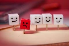 Le concept de la tristesse, solitude, déception Caractères formés des goupilles de bureau Fond rouge photographie stock